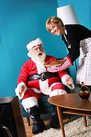Woman serving a pie to Santa