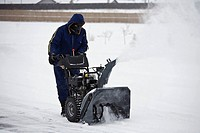 Man operating a snowblower