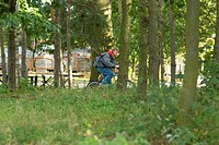 Boy on bicycle ridding through the city park
