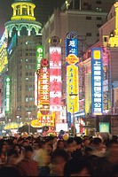 the Shanghai Nightlife With a Large Group of People Walking Along the Illuminated Streets, Side View, Long Exposure