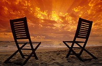 Two empty chairs waiting for you on the beach against a majestic orange dawn sky