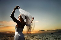Young adult female Caucasian bride holding out veil on beach.