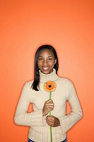 Portrait of African_American teen girl holding single Gerbera Daisy standing against orange background.