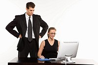 Caucasian mid_adult man with hands on hips looking over shoulder of woman sitting at computer.