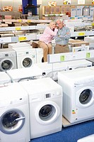 Mature couple shopping for appliances, woman embracing man with arms crossed