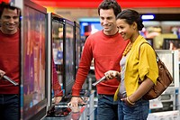 Young couple shopping for television, smiling, side view (thumbnail)