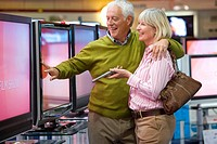Mature couple arm in arm shopping for television, smiling