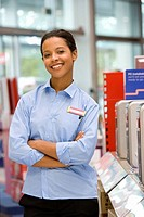 Computer saleswoman in shop with arms crossed, smiling, portrait