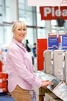 Mature woman shopping for computer, smiling, portrait (thumbnail)