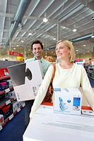 Young couple in shop with computers in boxes, smiling