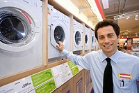 Young salesman by washing machines, smiling, portrait