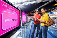 Young couple shopping for television, smiling, low angle view (thumbnail)