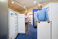 Mature couple shopping for appliances, smiling at each other, low angle view