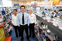 Young salesman flanked by female colleagues in shop, smiling, portrait