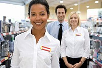 Young saleswoman by colleagues in shop, smiling, portrait