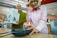Mature woman paying with chip and pin by man with boxes, smiling, low angle view