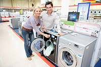Young couple shopping for washing machine, smiling, portrait (thumbnail)