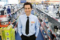 Young salesman in electronics aisle, hands in pockets, smiling, porttrait (thumbnail)
