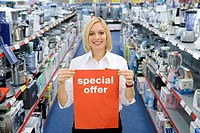 Young woman in electronics aisle holding 'special offer' sign, smiling, porttrait