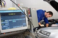Mechanic working on car by computer