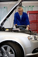 Mechanic with diagnostic computer by open bonnet of car, portrait, low angle view