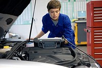 Female mechanic with diagnostic computer by open bonnet of car