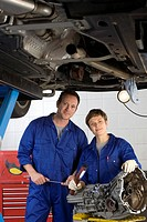 Female mechanic and colleague by elevated car, smiling, portrait