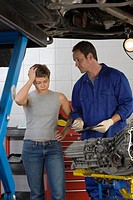 Woman with hand to head by mechanic with clipboard by elevated car (thumbnail)