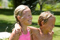 Brother and sister 7-11 arm in arm, smiling with eyes closed, being sprayed with water in garden