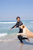 Woman in wetsuit playing with dog on beach (thumbnail)