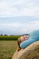Teenage girl 16-18 lying on back on bale of hay, smiling, portrait