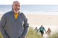 Senior man standing on beach smiling, portrait, family in background