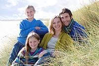 Couple with son and daughter 6-8 years sitting on long grass, smiling, portrait