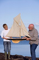 Senior man and grandson 7-9 years holding up model sailboat by sea, smiling at each other
