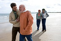Man and father walking on beach, smiling, two woman walking in background
