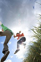 Father and daughter 7-9 years jumping from grass outdoors, low angle view (thumbnail)