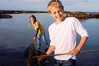 Boy and girl 7-9 years holding fishing nets in lake, smiling, portrait