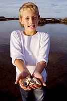 Boy 7-9 years standing by lake, holding sea shells, smiling, portrait