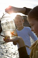 Girl 7-9 years holding up jar containing starfish by boy