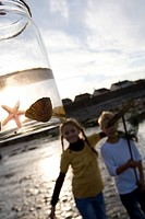 Boy and girl 7-9 years standing by jar containing starfish, smiling, portrait