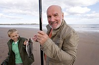 Grandfather and grandson 7-9 with fishing rod and fish on beach, smiling, portrait