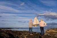 Senior couple with model boat on rocks by sea, rear view