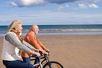 Senior couple cycling on beach, side view