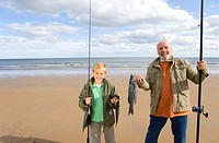 Grandfather and grandson 7-9 on beach with fishing rods and fish, smiling, portrait