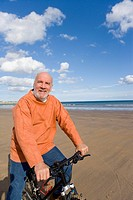 Senior man with bicycle on beach, portrait
