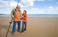 Grandfather with fishing rod smiling at granddaughter 9-11 on beach