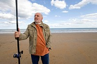 Senior man with fishing rod on beach, hand in pocket, low angle view