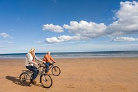 Senior couple cycling on beach, smiling at each other