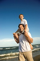 Caucasian father with pre_teen boy on shoulders on beach.