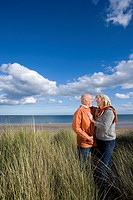 Senior couple arm in arm on sand dune, smiling at each other, side view